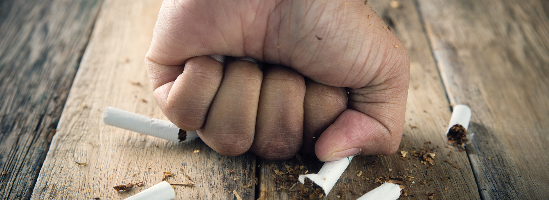 person smashing a cigarette with their fist